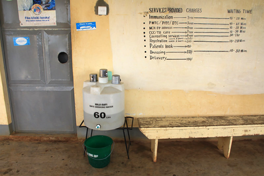Water station consisting of improved storage container with a narrow mouth, lid, and spigot on a metal stand.