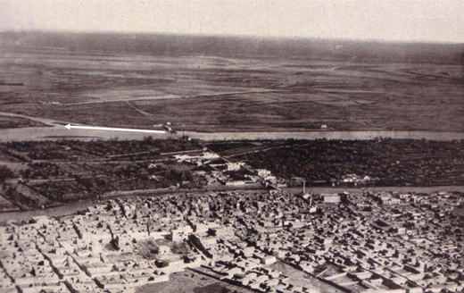 Panoramic photograph of the Euphrates River and the city of Deir Ez-Zor in 1920. The horizontal arrow points to the river island that is observed at the centre of previous photographs. Source:Blanchard (1929, p. 214).